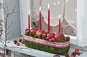 Adventsgesteck mit 4 Kerzen vorm Fenster