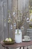 Osterstrauss aus Zweigen in alter Milchkanne, geschmückt mit Oster-Oblaten