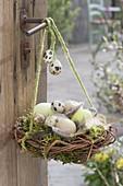 Osternest aus Zweigen und Moos, gefüllt mit Ostereiern