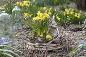 Osternest aus Gräsern, Zweigen und Moos im Garten