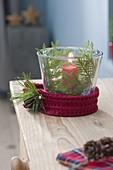 Glas mit roter Kerze als Windlicht, dekoriert mit Thuja (Lebensbaum)