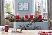 Rote Kerzen auf Rinde mit Picea (Fichte) Zweige mit Zapfen