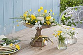 Gelb-weisser Kranz und Windlicht auf Holz-Schale mit Fuss