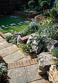 Treppe aus Schieferplatten und Klinker, gemauerte Hochbeete, kleine Rasen-Fläche mit Platten, Liguster-Stämmchen