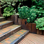 TIMBER DECKING LEADING TO BRICK STEPS, EDGED with WOODEN SLEEPERS. Designer: Vic SHANLEY