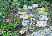 Pflasterung aus buntbemalten Keramikplatten und Keramikköpfen.