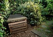 Abgedeckter Kompostbehälter zwischen Sträuchern verdeckt