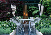 weiße Sitzgruppe auf blauem Granit, Hochbeete mit Gardenia jasminoides (Gardenien) und Lavendel (Lavandula), Säule aus Corten-Stahl als Wasserspiel, Acer palmatum (Fächerahorn)