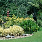 Japanisch gestalteter Teich mit Pseudolarix amabilis (Goldlärche), Phormium veitchii (Flachs) und Kieselsteinen