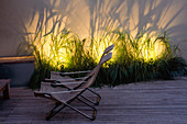TIMBER DECKING AND DECK CHAIRS with THE FOUNTAIN GRASS - PENNISETUM ALOPECUROIDES - Behind LIT UP. DESIGNERS PAUL THOMPSON AND TREVYN MCDOWELL. SHADOW