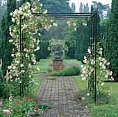 Metal ARBOUR with CLIMBING White ROSE 'Adelaide D'ORLEANS' OVER PATH at LOWER HALL Garden, SHROPSHIRE. Bronze SCULPTURE by PETER Ball
