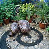 Kupferblech-Köpfe auf Kieselstein-Mosaik mit Spirale aus schwarzem Schiefer,