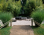 'Der Archipel' japanischer Garten mit Kies und Stein , Weg aus Brettern, Miscanthus (Chinaschilf) , hinten Bambus