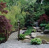 JAPANESE STYLE GARDEN. BAMBOO LATTICE GATE with WATERFALL IN THE BACKGROUND. HONDA Tea GARDEN. CHELSEA'95. DES:Julian DOWLE & K NINOMIYA