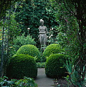 ARCHES AND CLIPPED Box BALLS CREATE VISTA TO Statue of Diana IN SHADY CORNER. Designer: Helen DILLON