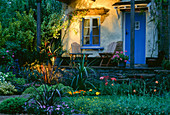 RAISED Patio & HOUSE with WOODEN CHAIRS. SUNKEN Garden with PHORMIUM & PAPAVER all LIT by Garden AND Security LIGHTING. MARIE CURIE'S 'Sun AWARENESS' Garden DES: PATRICK MCCANN