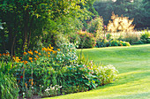 VIEW From Mixed HERBACEOUS BORDER, OVER THE LAWN, TOWARDS STIPA GIGANTEA. West SILCHESTER HALL, BERKSHIRE. Designer Jenny JOWETT