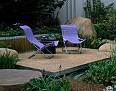 RSPB Garden, CHELSEA FLOWER Show 2002. Water Feature: RILL with WATERFALL SURROUNDED by Boulders, TERRACE with LILAC CHAIRS