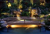 WOODEN BRIDGE OVER KOi POND.LIGHTING by Garden & Security LIGHTING. DESIGN by NATURAL & ORIENTAL Water GARDENS