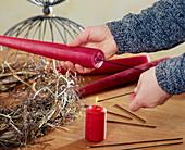 Adventskranz binden. 2. Step: Drahtspitze in Kerzenflamme erhitzen und in Kerzen