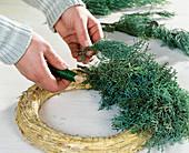 Adventskranz binden. 2. Step: Zweige auf Strohring legen. Abwechselnd eine ganze