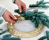 Adventskranz aus Nobilistannenzweigen binden. 1. Zweige mit grünem Draht an Stro