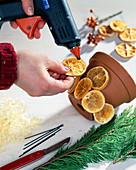 Kerzendekoration: 1. Step. Tontopf mit getrockneten Orangenscheiben bekleben.