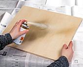 Adventskalender mit Tontöpfchen. 1. Step: Holzbrett mit Goldspray ansprühen