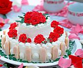 Torte mit roten Rosenblüten dekoriert