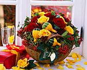 Korb mit Herbstgesteck aus Rosen, Zierkürbissen und Beerenschmuck