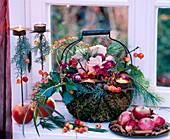 Metallkorb mit Moos ausgekleidet und Blüten und Zweigen geschmückt