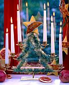 Kerzenhalter in Tannenbaumform mit Zweigen umwickelt und Sternen