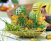Osterschale mit Weizengras, Eiern, Hühnchen und Bast