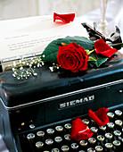 Alte Schreibmaschine mit Rosa / roter Rose