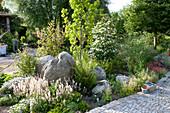 Schattiges Beet im Vorgarten mit Gehoelzen, Stauden und Findlingen