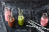 Colourful smoothies with banana, pineapple, spinach, rocket and raspberries (vegan)