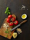 Tomaten, Basilikum und Parmesan auf Holzbrett, danben Zitrone, Pinienkerne und Olivenöl
