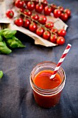 Tomato juice in a glass with a straw