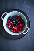 Summer berries in a light blue colander