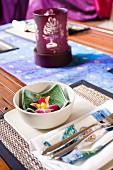 Asiatisch gedeckter Tisch mit Essschälchen, Besteck und Teelicht