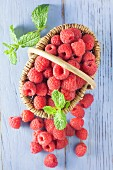 Raspberries in a basket on a blue wooden background