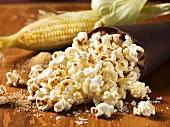 Popcorn, im Hintergrund Maiskolben
