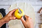Frau schält gelben Apfel für Apfelkuchen