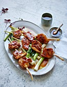 Chicken and lemongrass skewers on a bed of spring onions (low carb)