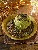 A braised savoy cabbage head garnished for Christmas