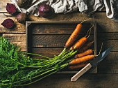 Fresh garden carrots in a wooden tray and beetroots against a rustic wooden background