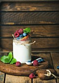A glass jar of white yoghurt with fresh berries, peach and mint leaves on a wooden board