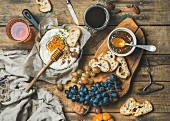 Camembert in small pan, honey, fig jam, grapes, grilled baguette slices and a glass of rosé wine