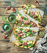 Parma ham, fig, rocket and sage flatbread pizza cut into pieces