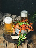 Two pints of wheat beer and boiled crayfish with lemon and parsley on a round, dark wooden serving board